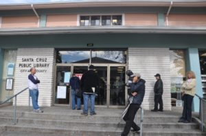 visitors wait outside the locked Santa Cruz Library, waiting for them to open. Administrators are working to complete a budget in the face of even more cuts. Photo by Morgan Grana.