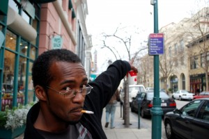 A man smoking on Pacific Avenue points out the law. The smoking ban, seen on the sign, went into effect on Oct. 20 after a one month grace period. CHP Archives.