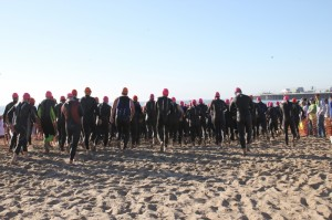 Racers in wetsuits run into the open arms of the ocean. Photo by Asa Hess-Matsumoto.