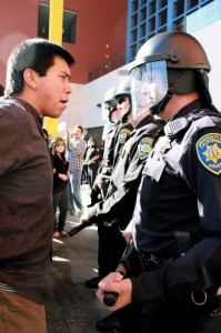 [Photo of a protester standing in front of a police line.]