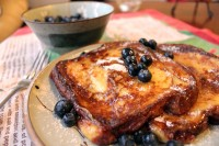 French toast, served with syrup, blueberries, and powdered sugar.
