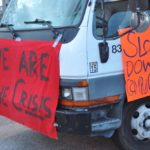 Signs posted on a van associated with the barricade. Photo by Mikaela Todd.