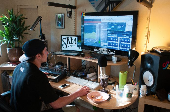 Sam F works with his production setup in his house