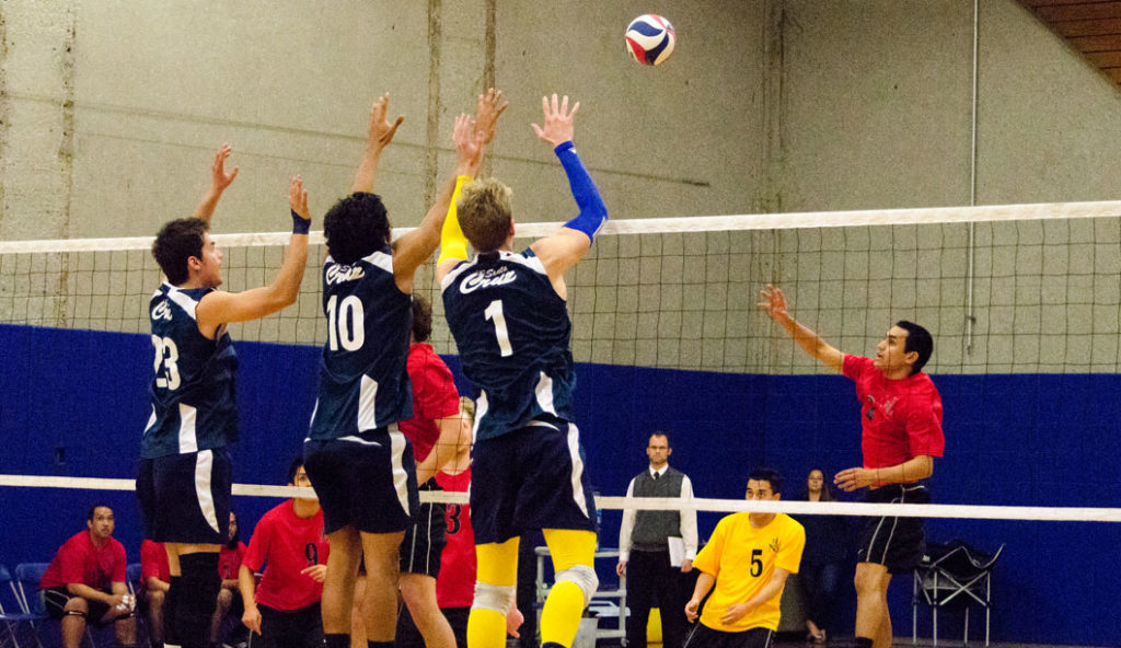 Jake Landel (#23), Branden Torado (#10) and Harley Frost (#1) team up for a block against Holy Names outside hitter. Photo by Jessie Case.