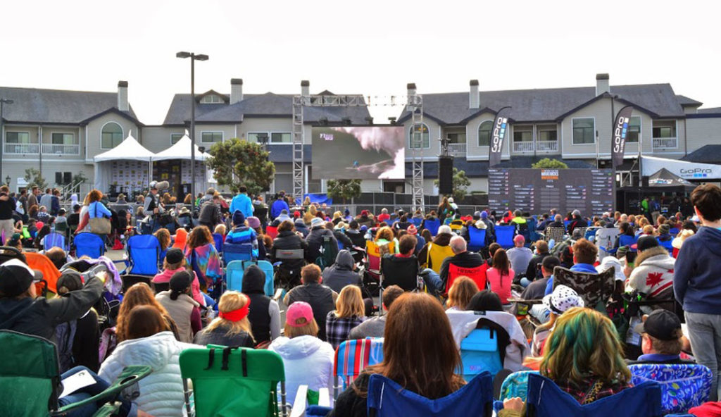 The crowd watches the event on the Jumbotron in the parking lot of the Oceano Hotel, as the cliffs prevent large crowds from watching at Pillar Point. Photo courtesy of Derrick Thompson.