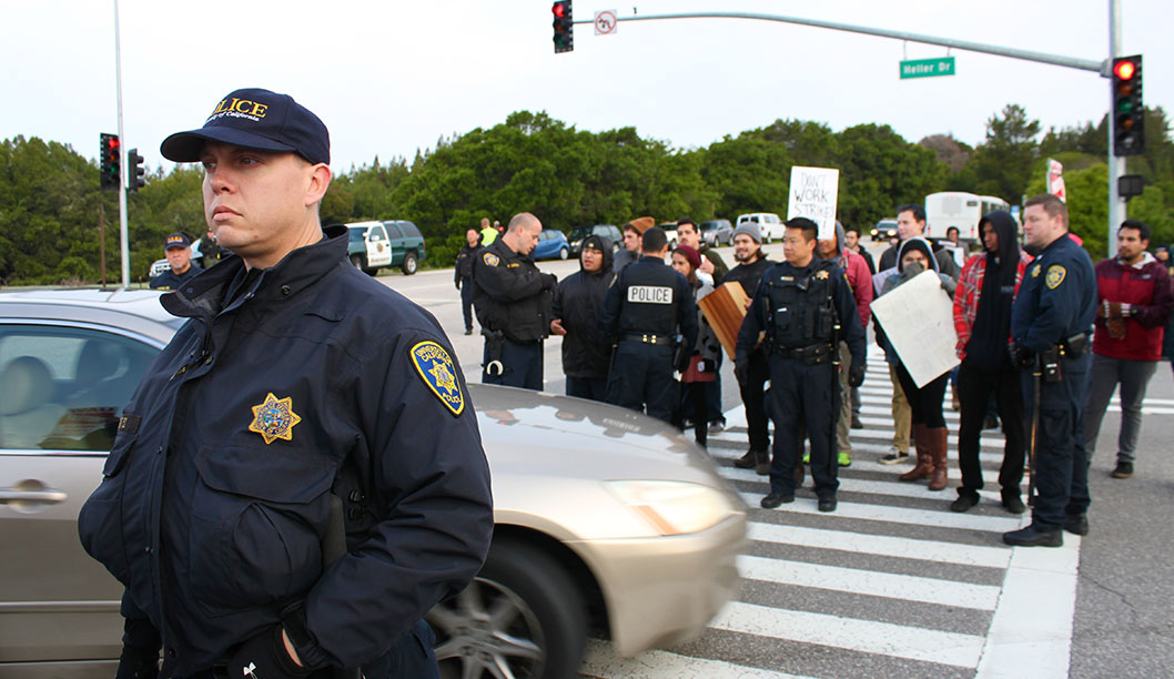 During the United Auto Workers 2865 strike, police break up the picket line to allow cars to enter campus through the West Entrance on April 3. Photo by Katie Small.