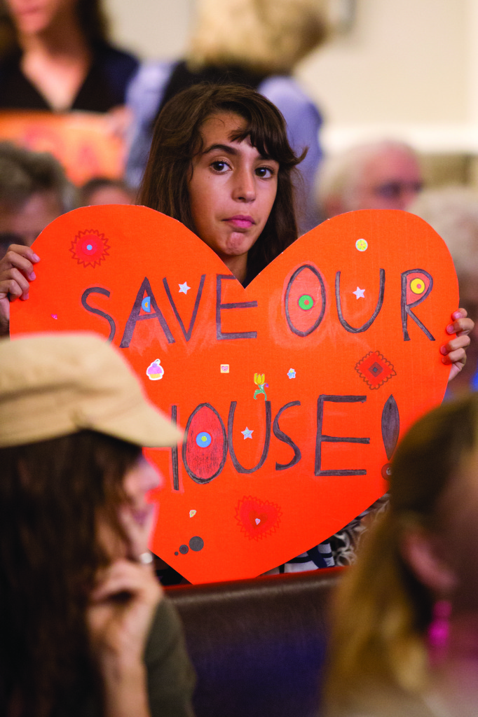 "Among the crowd of protesters, Isabella, daughter of Paula Gregoire, holds a ""SAVE OUR HOUSE"" sign in objection to the proposed housing ordinances that would affect the existence of her current housing."