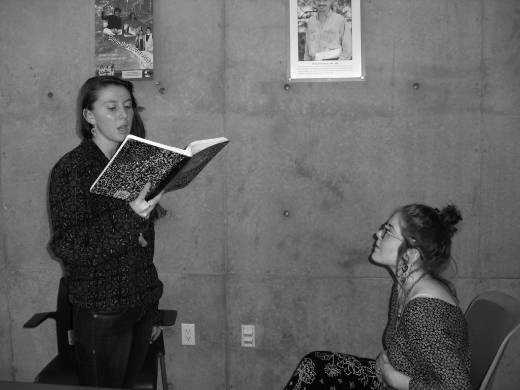 Jacqueline Grohs (left) shares her poetry with fellow KPP organizer Alexandra Moskow (right). Photo by Gabrielle Garcia.