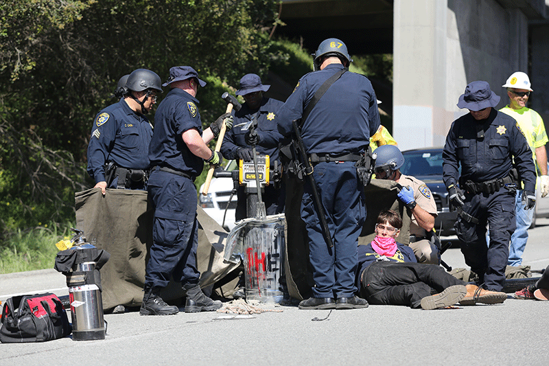 The officers also used a pry bar and hammer to peel back the sides of the garbage bins. Photo by Stephen De Ropp.