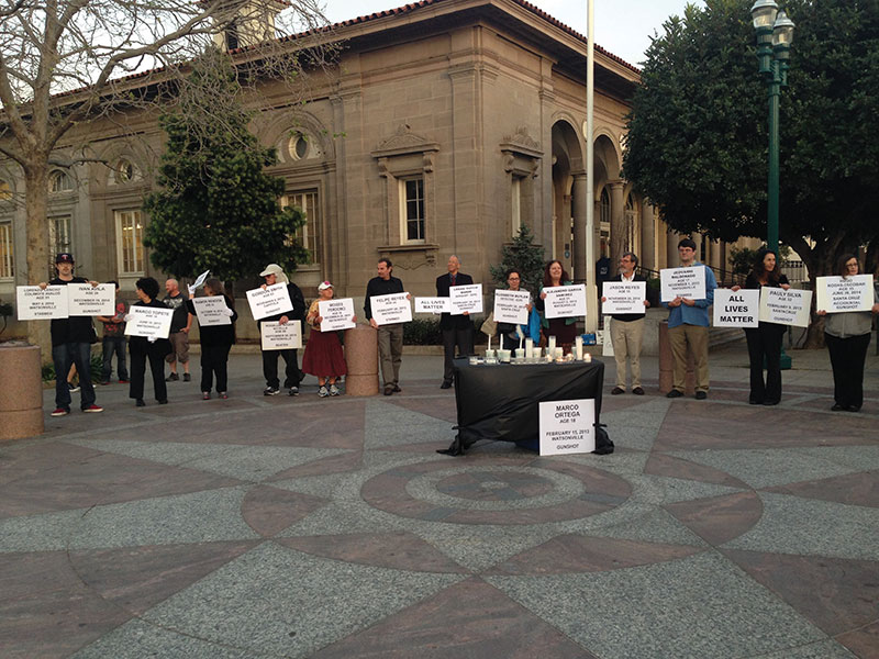 Individuals hold signs with names, ages and causes of death in a vigil organized by the Alliance for Peaceful Communities to honor victims of homicide in Santa Cruz County. Photo by Georgina Sandoval.