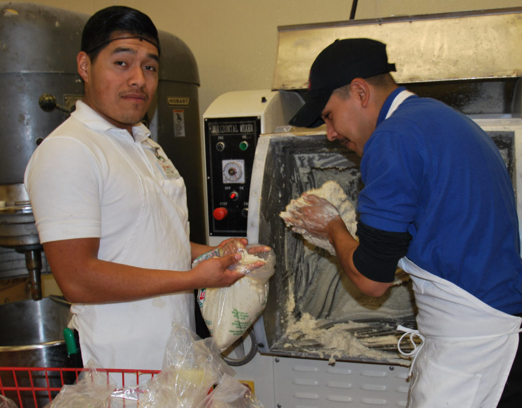 Two bakers knead dough in the bakery section of a Watsonville grocery store. Courtesy of Christine Peterson.