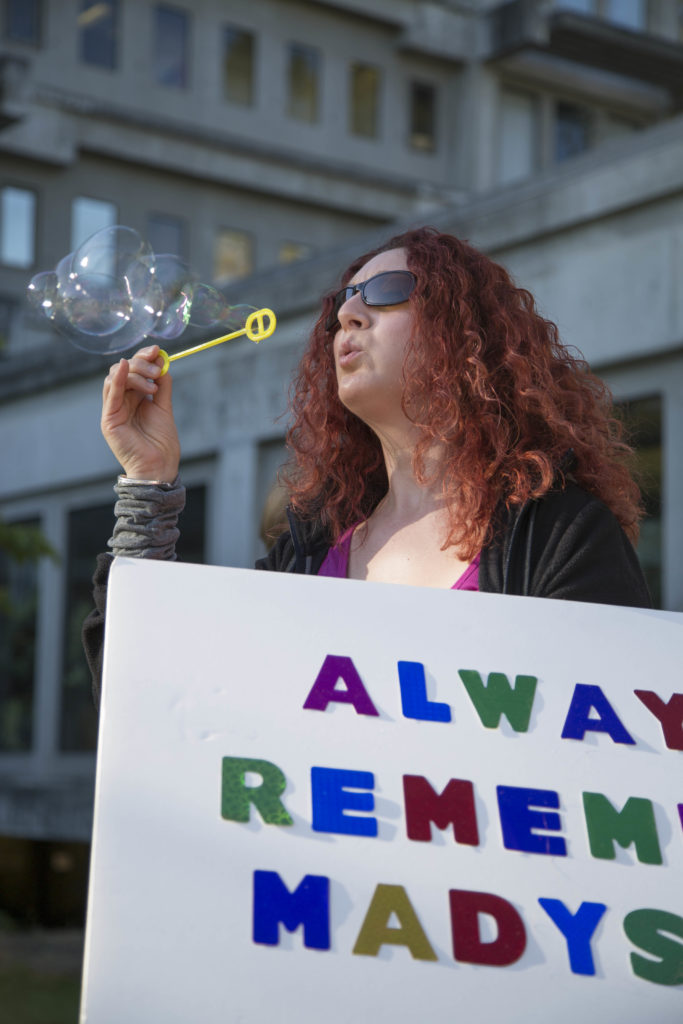 """Attendees blows a stream of bubbles above the courthouse. """"[Bubbles are] light and sweet, like children are — like Maddy was,"""" one resident said. Photo by Jasper Lyons."""