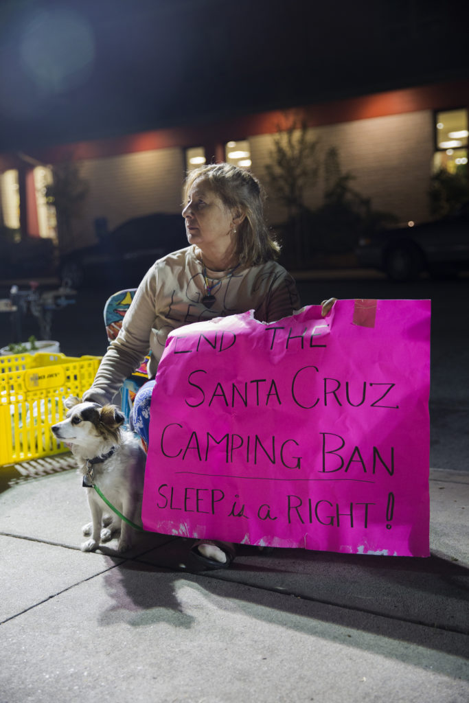 A woman sits outside of Santa Cruz City Hall to protest the Santa Cruz law that makes camping out in public spaces an offense. To draw attention to the law, protesters have been gathering outside of City Hall since the Fouth of July and planning sleepouts in front of the building. Photo by Casey Amaral.