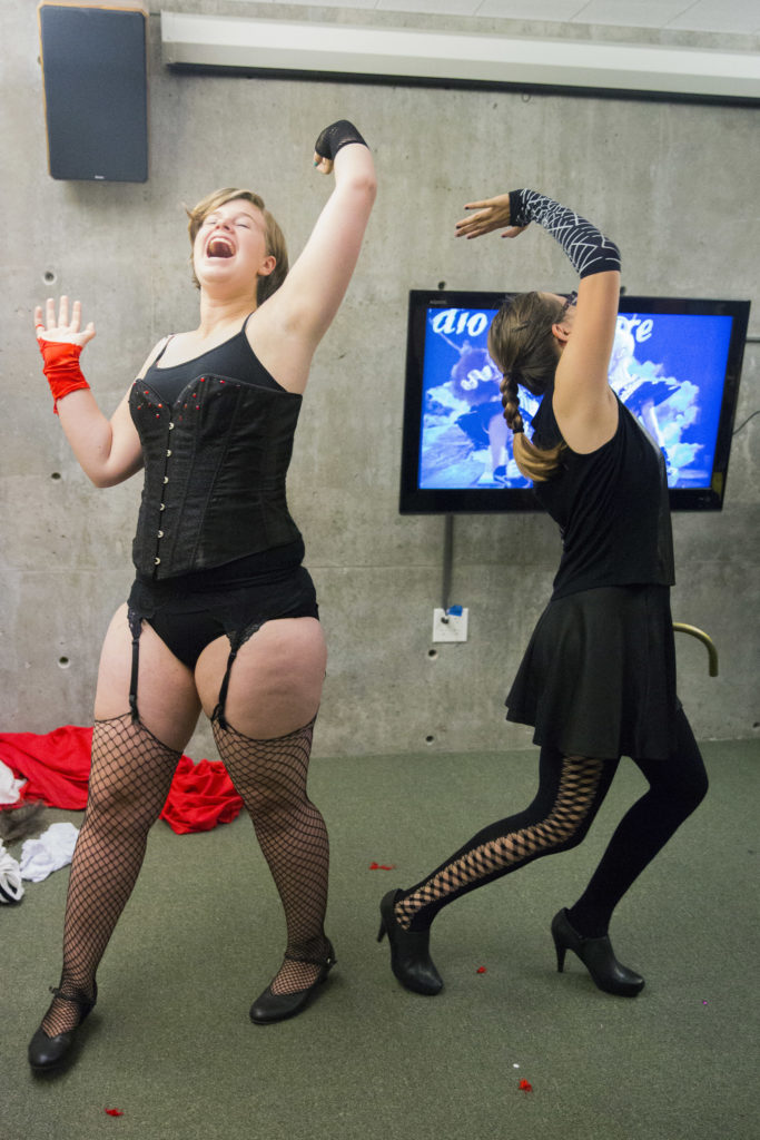 Slugs in Fishnets members Kayla Garvis, left, and Maya Lopez, right, practice for their upcoming performance by acting out the entirety of the Rocky Horror Picture Show in front of a TV screen to an audience of backstage workers and other cast members. This year they piled into a study room in McHenry Library to rehearse — feather boas, empty wine bottles and other props lining the corners of the room. Photo by Casey Amaral.