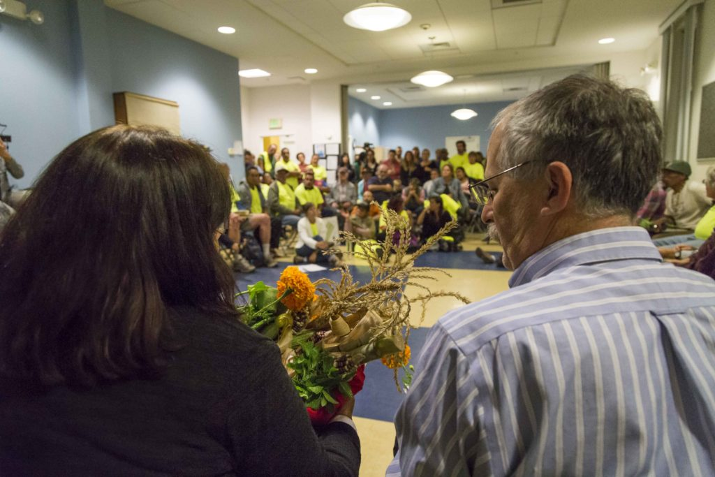 Mayor Don Lane(right) and Santa Cruz director of parks and recreation Dannettee Shoemaker(left) receive a basket of corn, beans, sugar cane, flowers and other organically grown goods from the farm while community members and supporters watch.