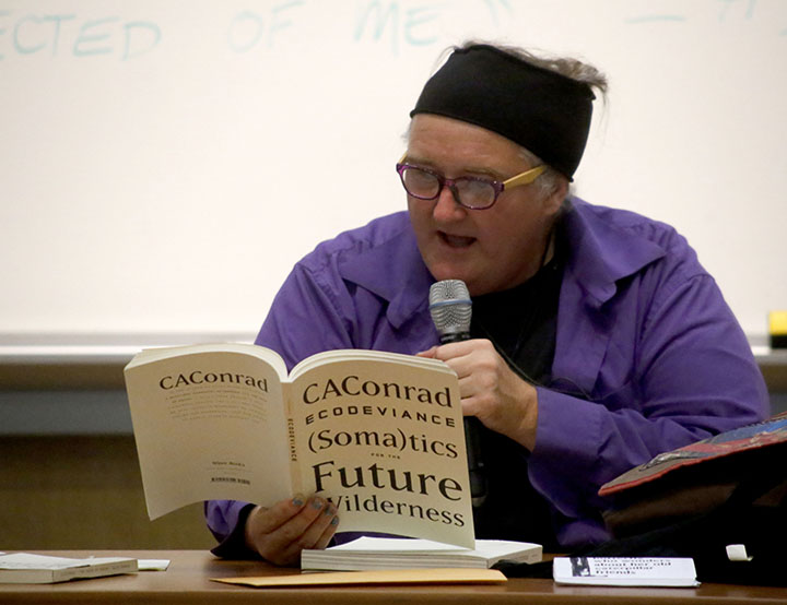 Poet CAConrad reads one of their book of poems to the audience last Thursday night for the first Living Writers Series of the school year. Photo by Calyse Tobias.
