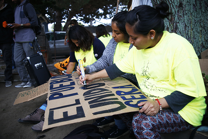Community members help to draw signs for the Beach Flats march. Photo by Calyse Tobias.