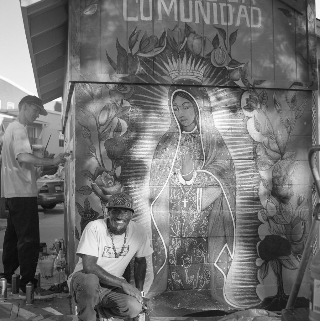Marciano Cruz retouched the Virgin of Guadalupe mural in the past. This time, Guadalupe is painted bigger and brighter. Photo by Ramona Parrotta