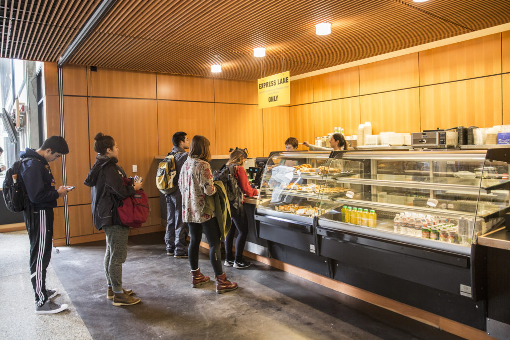 Students line up in McHenry Library during the reopening of Global Village Cafe. The cafe is now under management of Amazon Juices. Photo by Casey Amaral