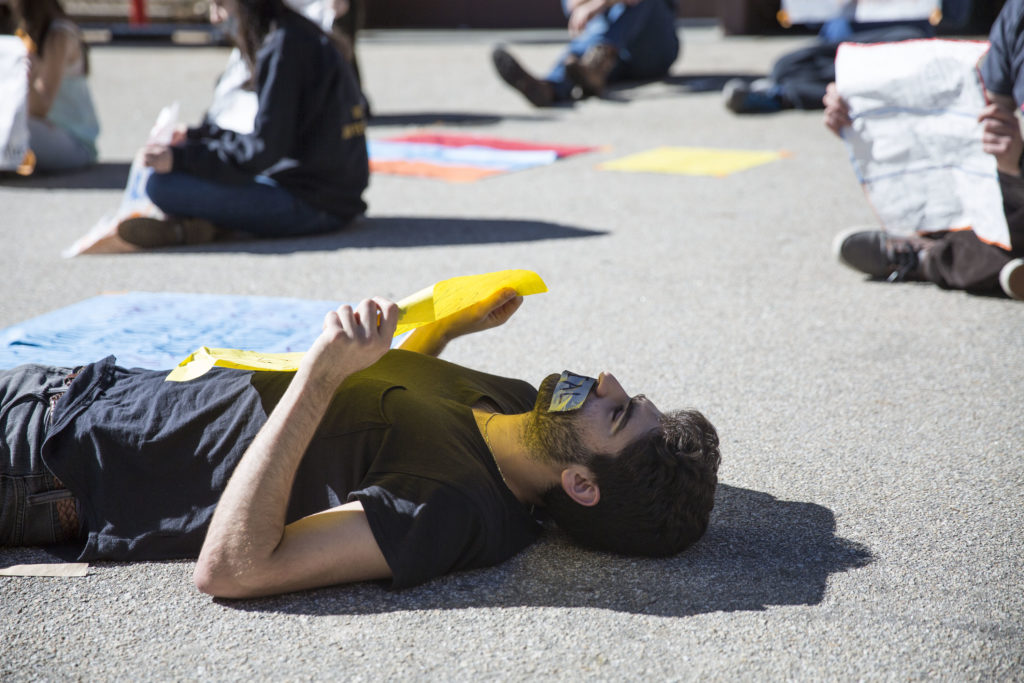 "A student laid on the ground in the middle of the Quarry Plaza holding a sign that read ""Are your hands clean?"" Photo by Casey Amaral."