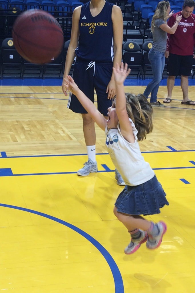 Four-year old Hazel Kent shoots the ball at one of  UCSC women's basketball's game day clinics this past year. Photos courtesy of Todd Kent.