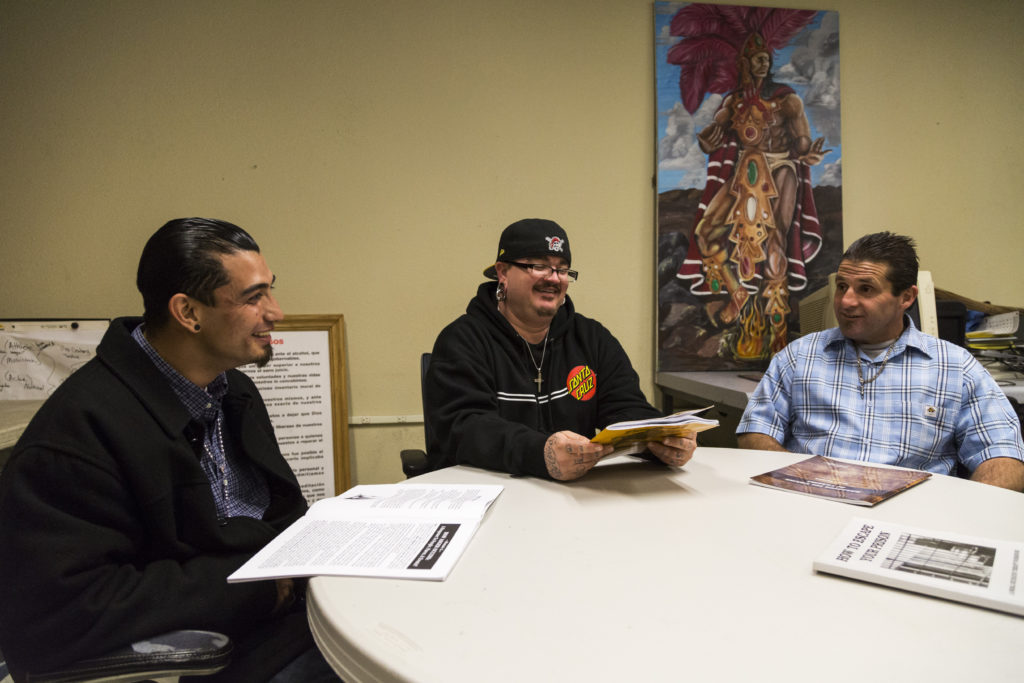 Three participants of Barrios Unidos' AB109 adult reentry program go over workbooks titled