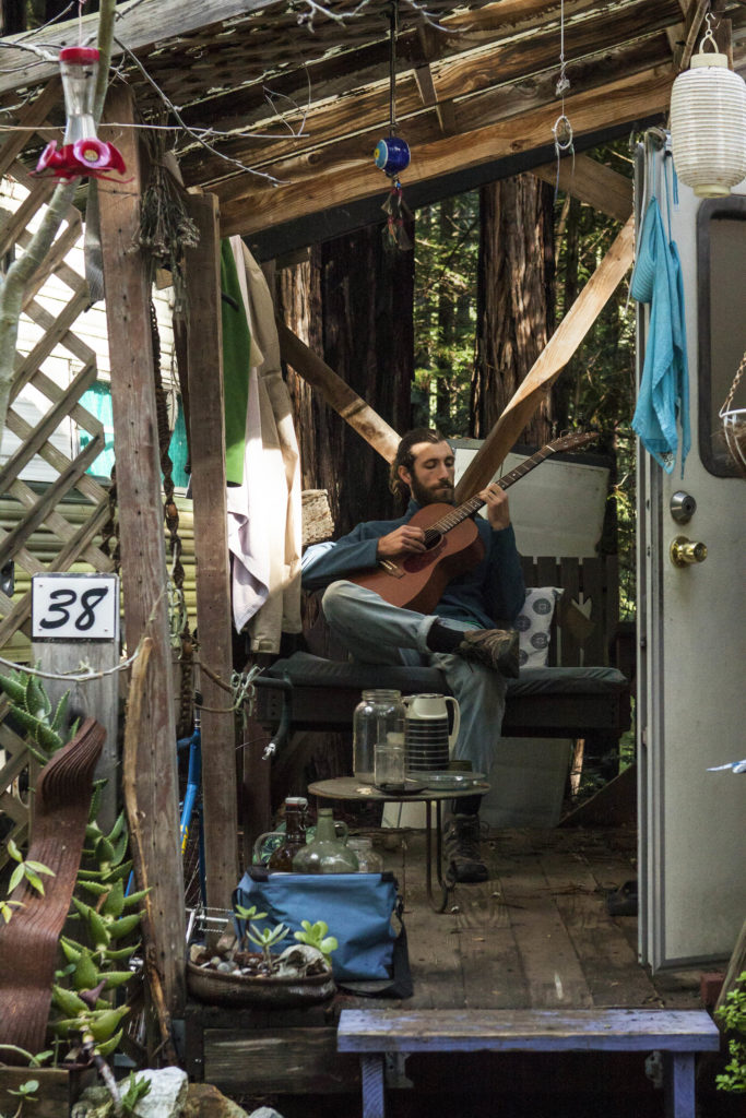 Trailer park resident Miro Hornberg relaxes outside of his trailer on his porch. Photo by Ali Enright.