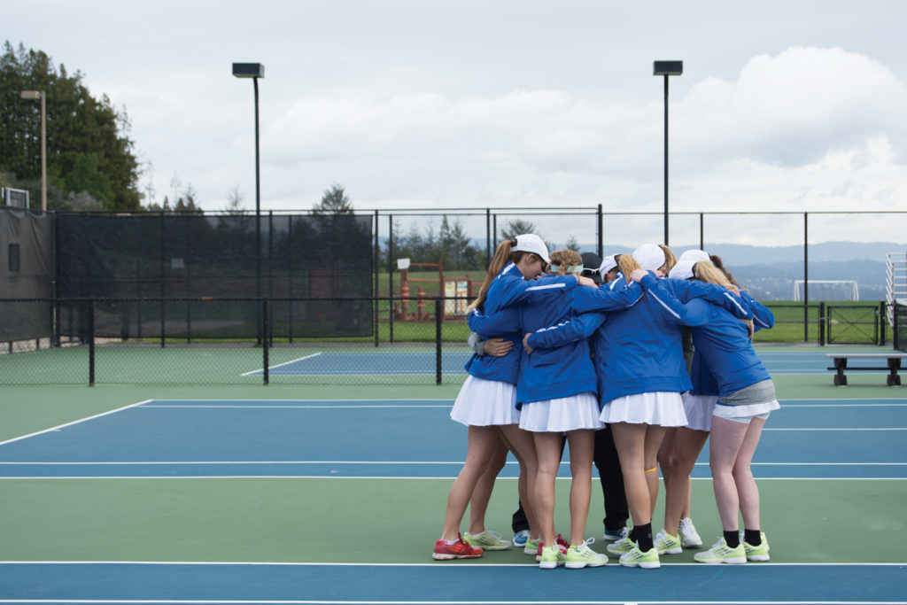 UCSC's women's tennis team and new coach Amy Jensen come together in a team huddle before starting their match against La Verne on Saturday. Photo by Megan Schnabel