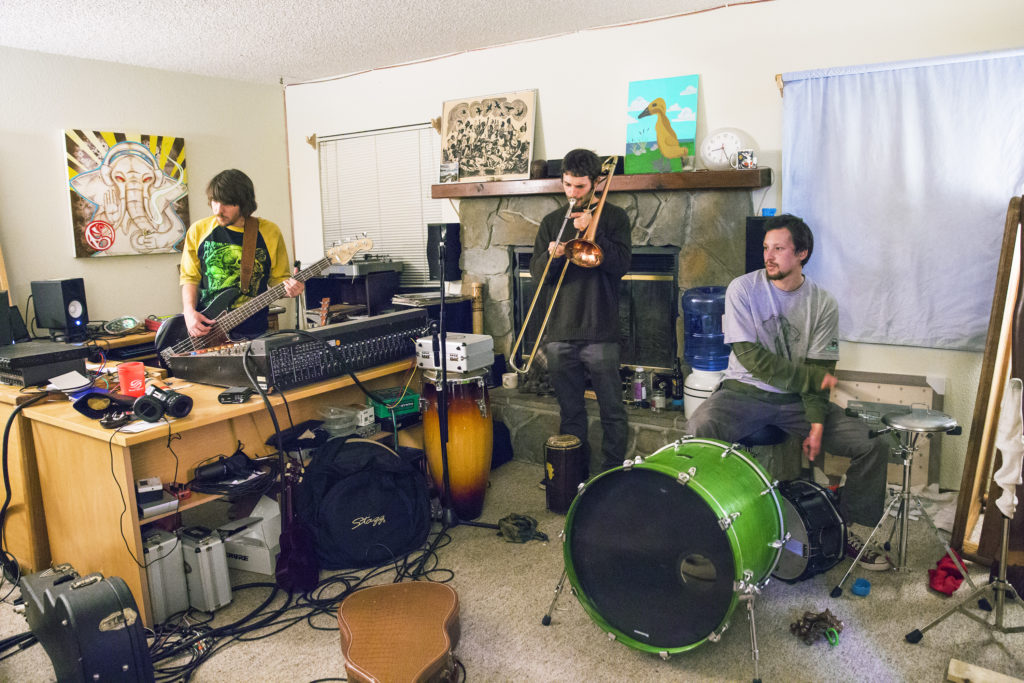 Local Santa Cruz band, Boostive, practices in their makeshift living room studio. Bandmates Brian McNamara (bass), Nathan Kocivar (trombone, right and saxophone, left) and Seiji Komo (drums) begin their practice session by switching instruments with each other and freestyling their set. Photo by Casey Amaral