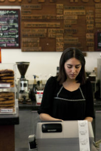 Stevenson Coffee House employee Diana Jimenez rings up a customer on Tuesday afternoon. The employees have initiated a petition to keep the shop open and have received over 2,500 signatures. Photo by Ali Enright