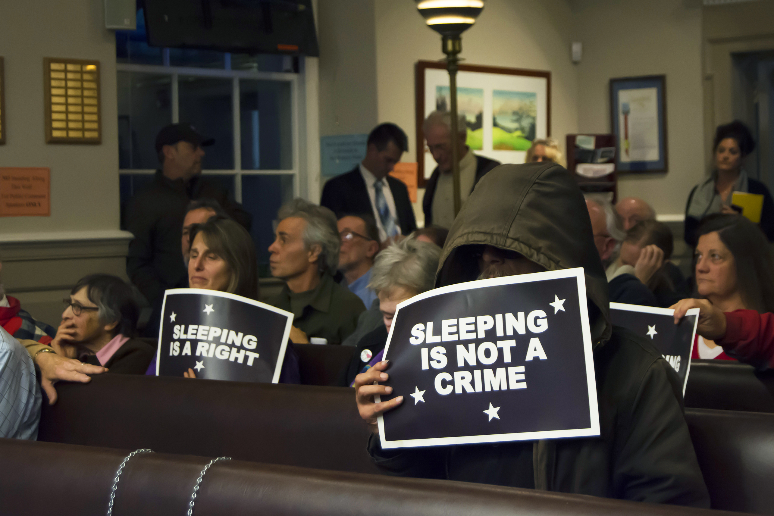 The majority of people who attended the city council meeting on Tuesday night were members of the public in support of the proposal. Many of them held signs to express their stance against the sleeping ban and criminalization of houseless people. Photo by Megan Schnabel