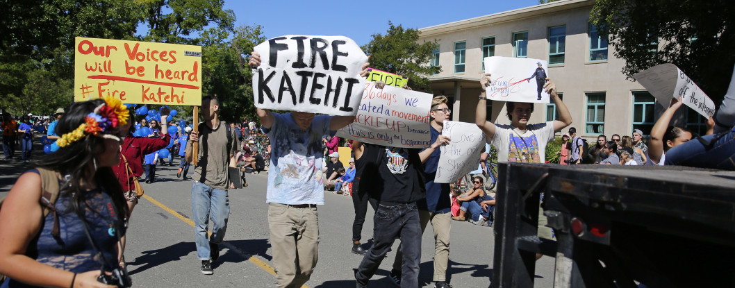 """About a dozen protesters briefly disrupted the 2016 Picnic Day Parade before forming their own """"Fire Katehi"""" float. The protesters were seen by tens of thousands of onlookers as they walked the lengths of the several mile long parade. Katehi, however was escorted away by her security before the parade began. Photo by Stephen de Ropp"""