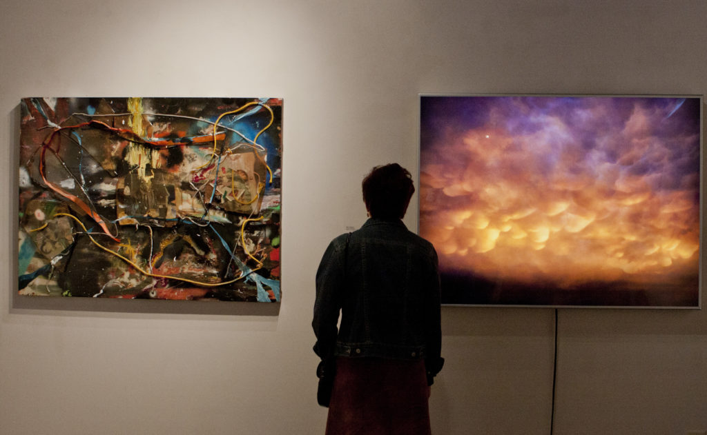 "Guests enjoyed artwork in various mediums including videos, t-shirts, and paintings. Associate professor Elliot Anderson's piece"" Clouds Averaged explores environmental-art activism through its mixed medium format of a digital photograph and lightbox. Photo by Ali Enright"