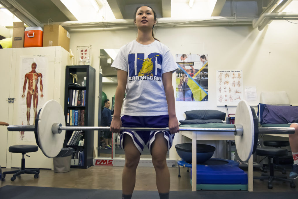 Kim Tom is one of six interns at UCSC's sports medicine clinic, as well as an athlete for the women's basketball team. Along with helping other athletes, she works on her own strength training and flexibility in the clinic. Photo by Megan Schanbel.