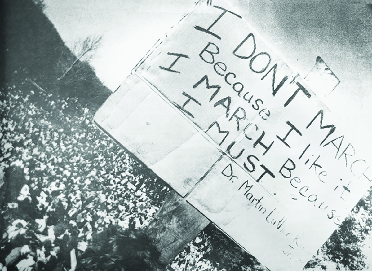 A Marcher in Santa Cruz held a sign in front of a sea of Gulf War protesters on Jan. 17 1991. Over 3,000 people rallied in the streets to show their outrage over the start of the war. Photo courtesy of UCSC Special Collections.