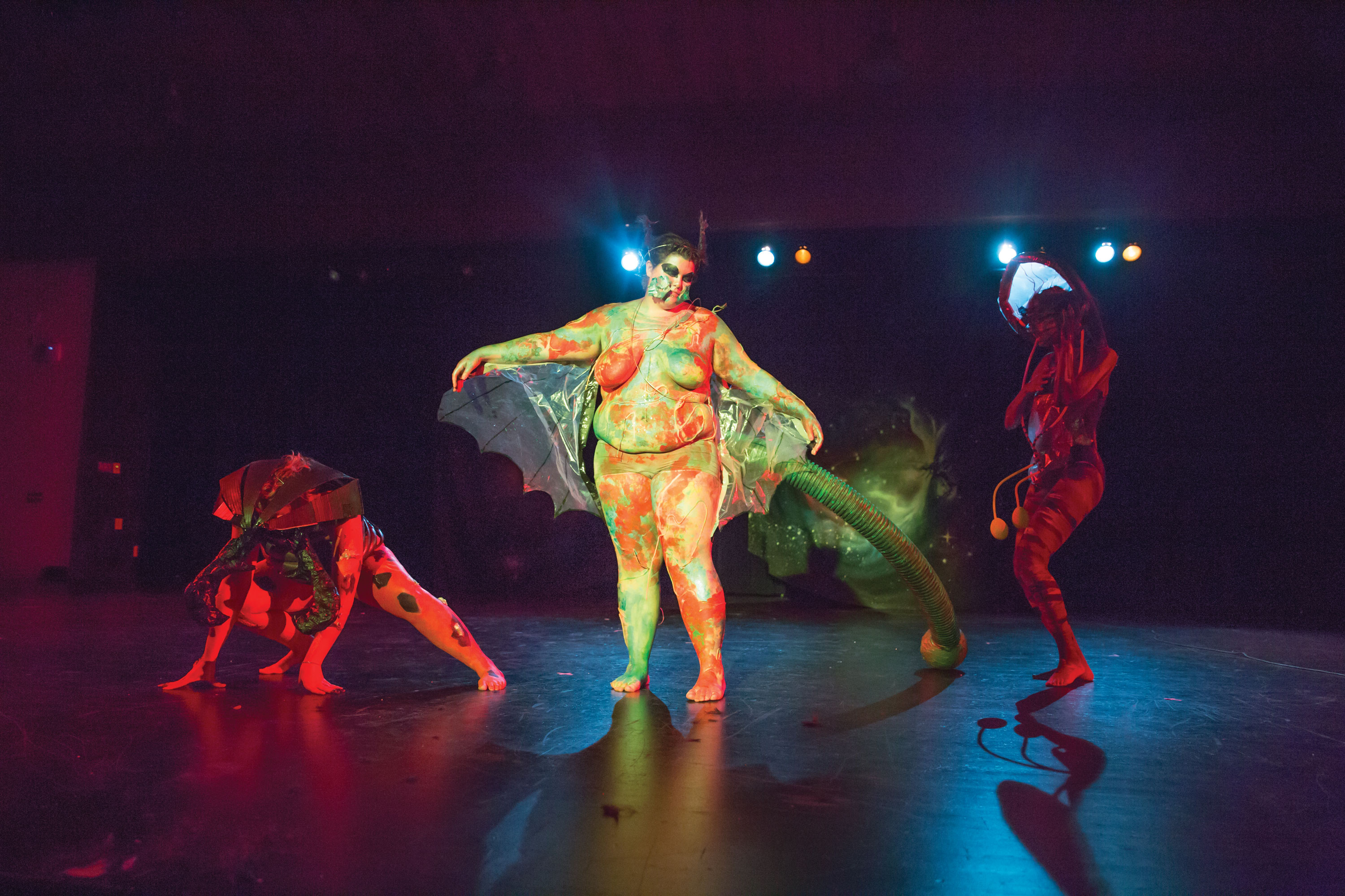 Performers dressed as alien-like bugs stumble across the stage.  Photo by Casey Amaral.