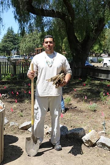 Amah Mutsun tribal member Matt Lopez holds a tule reed mat at the tribe's work day in San Juan Bautista on April 30. The Mutsun traditionally wrapped tule reed mats around a wooden foundation to create housing. Photo of Stephen de Ropp.