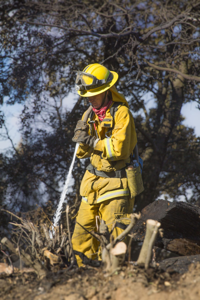 A firefighter extinguishes embers from the western edge of the fire perimeter. Photo by Casey Amaral.