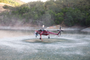 A Cal Fire helicopter collects water from the Almaden Reservoir to drop on the fire. Photo by Casey Amaral.