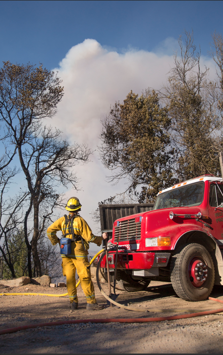 A firefighter extinguish embers from the western edge of the fire perimeter. Photo by Casey Amaral.