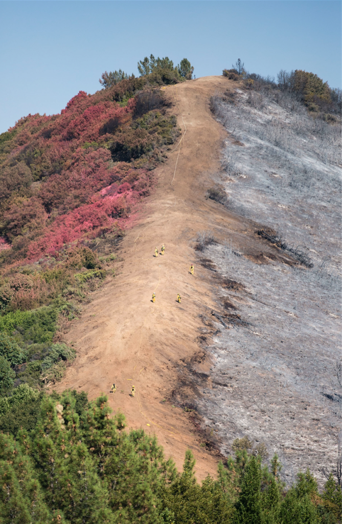 Firefighters work along the Loma Prieta ridge line, with its left side dosed in red fire retardant. Photo by Casey Amaral.
