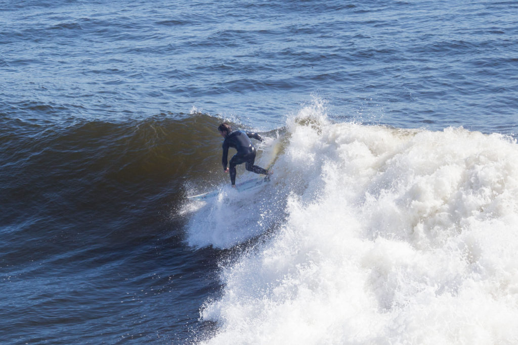 A surfer rides the waves at Steamer Lane, a famous point along West Cliff. The growing UC Santa Cruz Competitive Surfing Club hopes to bridge the gap between local and student surfers, despite some locals' concerns about overcrowding. Photo by Calyse Tobias
