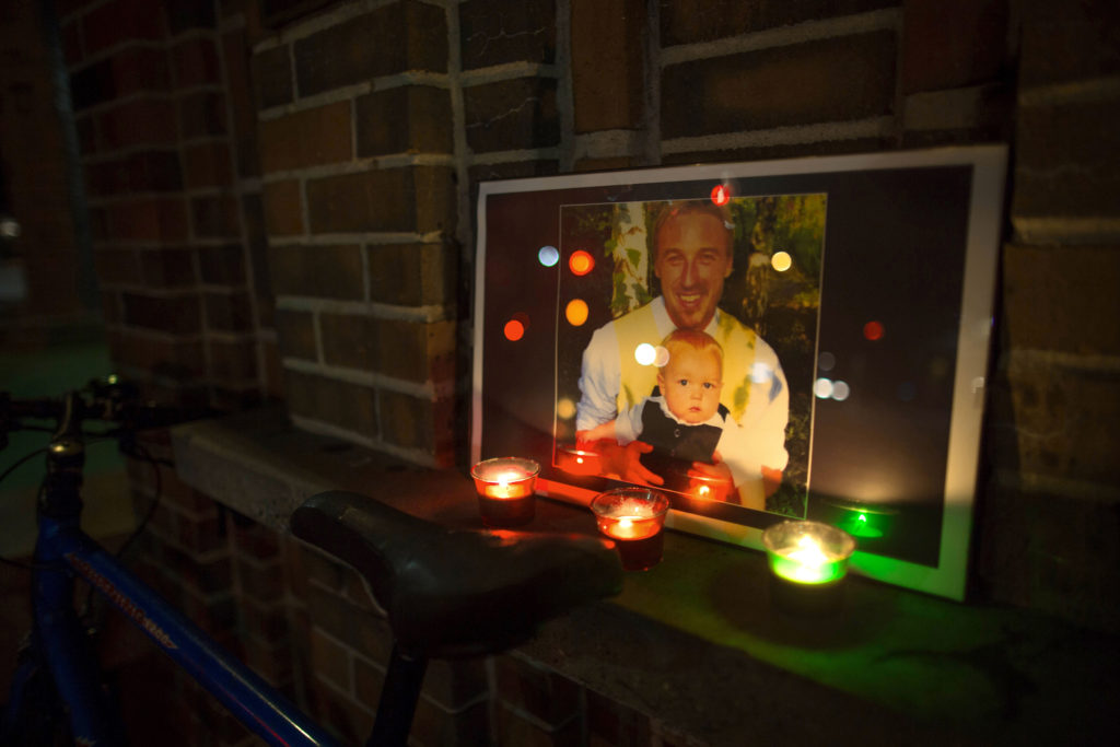 A photo of Sean Arlt and his son sits on the edge of the clock tower with candles at the Love Manifesto vigil held on Oct. 23. Photo by Matthew Forman