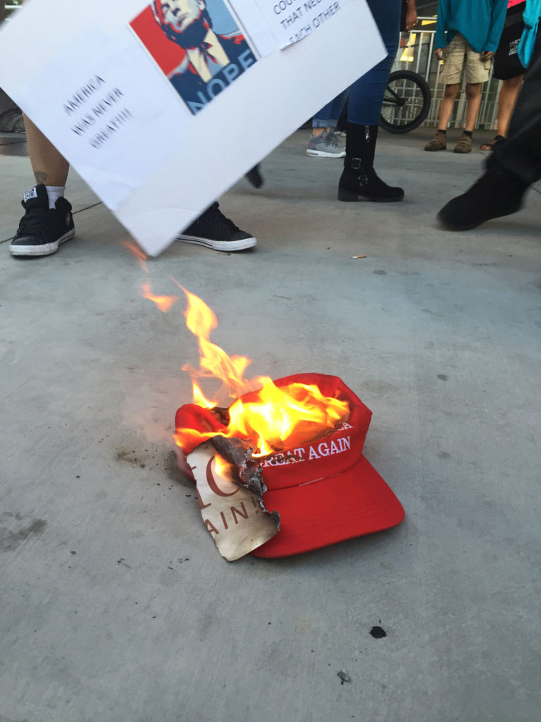 "One of Donald Trump's signature ""Make America Great Again"" hats burns in the street, snatched and set ablaze by protesters outside the Trump rally in San Jose on June 2. Photo by Samantha Hamilton."