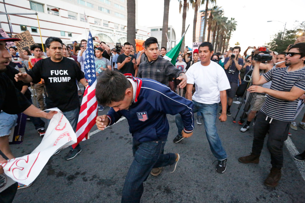 At times, the scene turned violent in the streets outside the San Jose Convention Center after the June 2 Donald Trump rally, as hundreds of protesters confronted rally attendees as they left.  Hundreds of police officers clad in riot gear responded, but countless fights still broke out and few were arrested.  A month later, several rally attendees filed a class action lawsuit against the city of San Jose, its mayor and its police chief for failing to prevent the violence. Photo by Stephen de Ropp.