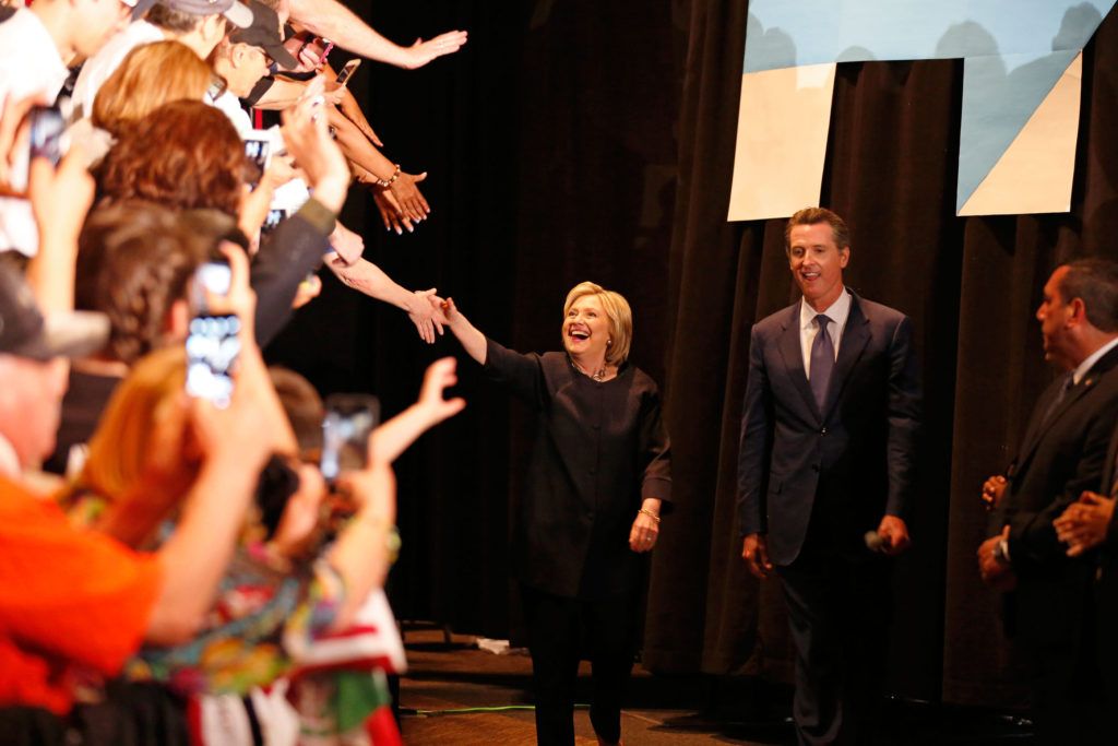 "Hillary Clinton makes her entrance during a campaign stop in downtown San Jose on May 26 (left). Donald Trump riles up the several thousand in attendance at his rally in San Jose on May 26.  Trump took a decidedly more aggressive tone than in the past declaring that ""Hillary Clinton needed to go to prison"". Photo by Stephen de Ropp."
