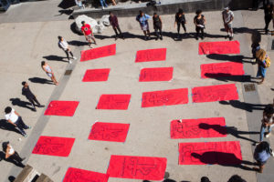 Members of A/BSA gathered around paper cutouts with chalk outlined bodies representing victims of police brutality, prepared to lay down. Later, the students shared stories about them. Photo by Calyse Tobias