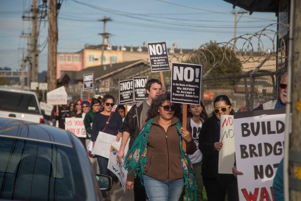 Residents march through traffic to Granite Construction's Headquarters in Watsonville to protest the company's bid to build Trump's wall. Photo by Matthew Forman
