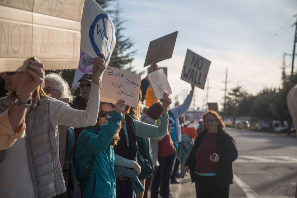 Marchers walk along the streets and  hold up signs to passing cars while showing their support for the protest against the Watsonville construction company. Photo by Matthew Forman