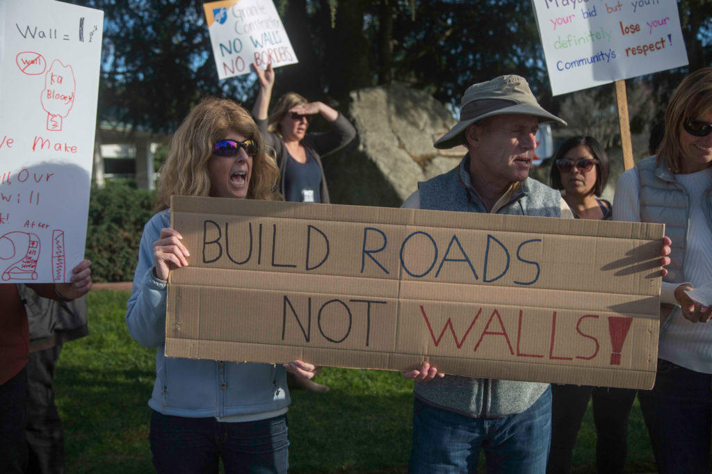 Two protestors hold up a cardboard sign toward oncoming traffic to boycott the construction company's recent bid.